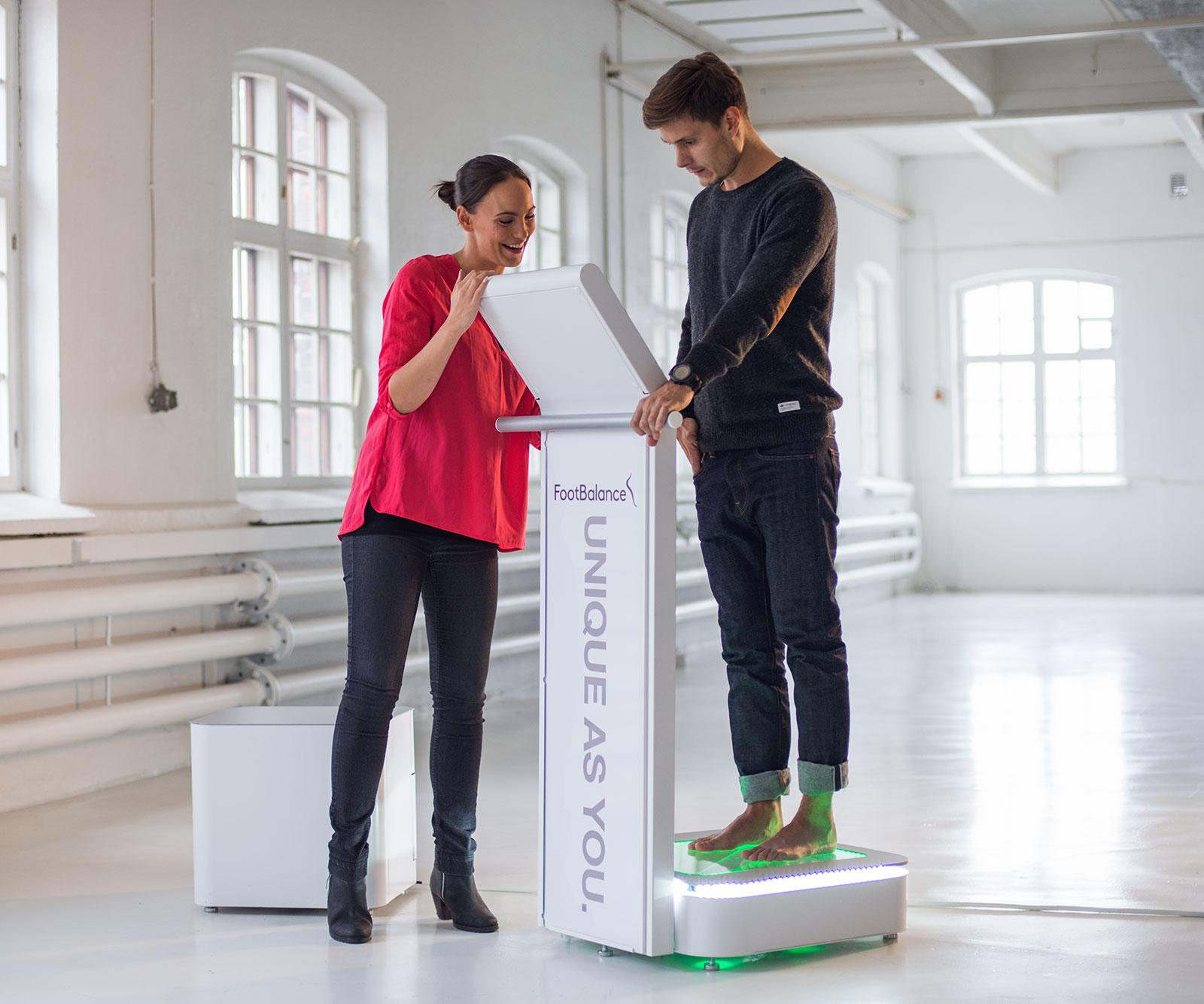 A woman and man doing a FootBalance foot scanning and analysis