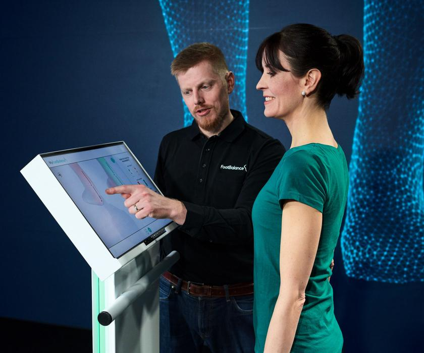 Two people making a foot analysis on the MyFootBalance scanner