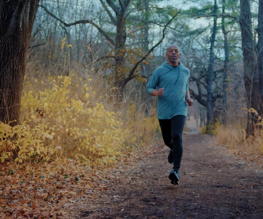 A coloured man running in the woods